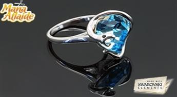 """Apzeltīts kulons """"Kārdinātaja"""" ar interesantu dizainu un gaiši zilu Swarovski Elements™ kristālu."""